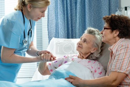 Photo for Doctor talking to elderly patient lying in bed in hospital - Royalty Free Image