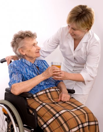 Young nurse encouraging senior woman in wheelchair