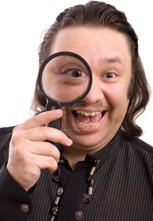Photo pour Homme drôle tenant loupe avec expression heureuse . - image libre de droit