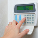 Female hand arming a burglar alarm system...