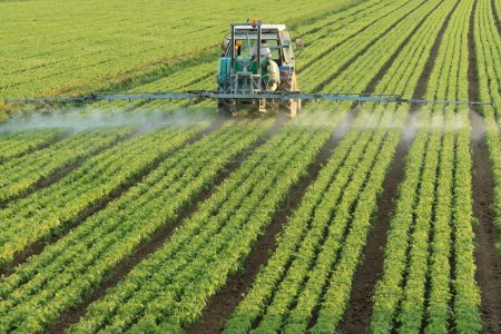 Photo for Farming tractor spraying a field - Royalty Free Image