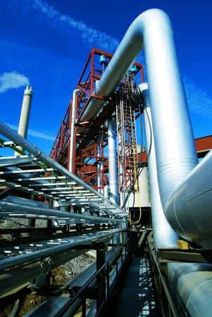 Photo pour Zone industrielle, pipelines en acier, cheminée et vannes contre le ciel bleu - image libre de droit