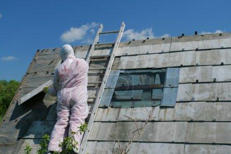 Photo pour Travailleur d'enlèvement de l'amiante. Élimination des déchets dangereux - travaux professionnels à l'architecture ancienne . - image libre de droit