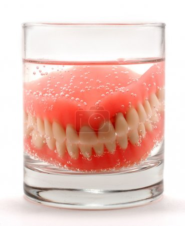 Dentures placed in a glass of water for cleaning...