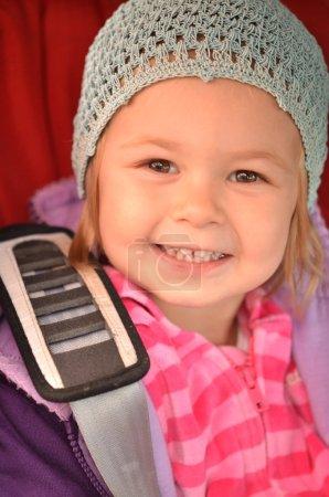 Little girl sitting in car safety seat.shot made through window pane