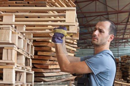 Man arraging pallets, horizontal shot