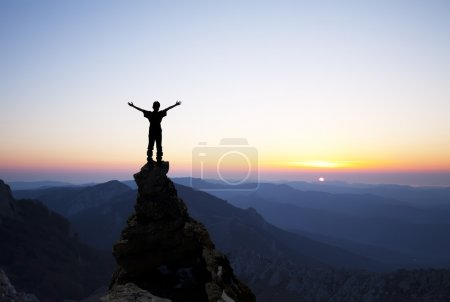 Photo for Man on top of the mountain reaches for the sun - Royalty Free Image