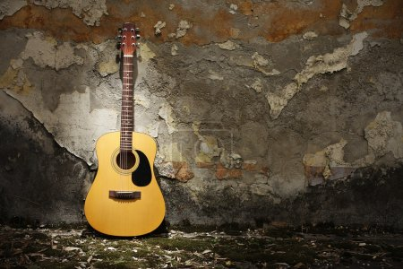 Photo for Acoustic guitar leaning on grungy wall - Royalty Free Image