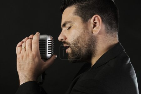 Portrait of male singer with old fashioned microphone
