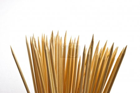 Many wooden bamboo skewers against solid white bac...