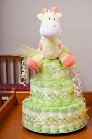 Photo pour Gâteau à couches neutre pour le genre vert et jaune avec girafe en peluche jaune sur la table à langer pour bébé - image libre de droit