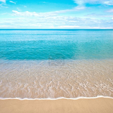 Beautiful sandy beach with calm water against blue skies.