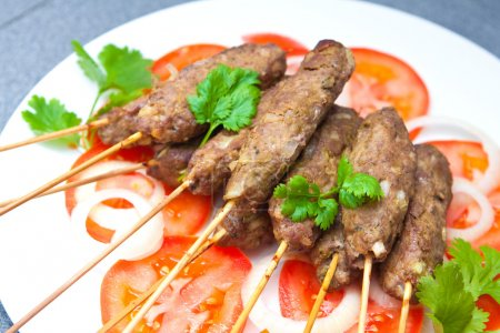 Delicious lamb seekh kebabs served with rice and tomatoes