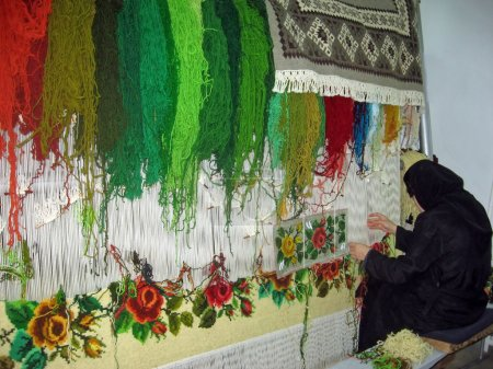 Woman who works the colorful wool and she produce carpets