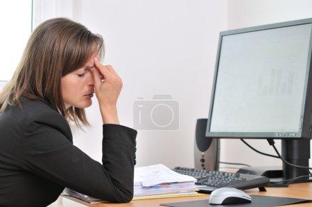 Foto de Mujer de negocios joven con dolor de cabeza y los ojos cerrados cansados sentado en el ordenador en lugar de trabajo - Imagen libre de derechos