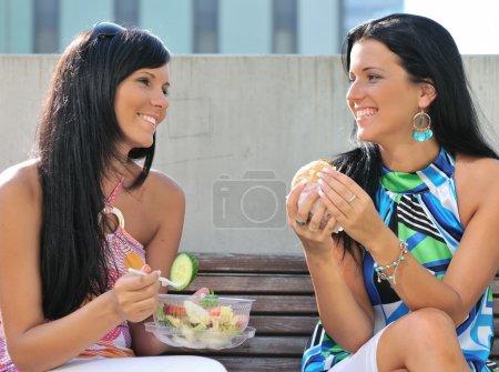 Photo pour Deux amis - souriant jeunes femmes manger ensemble à l'extérieur sur la journée ensoleillée - image libre de droit