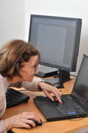 Photo pour Jamais assez vieille - femme âgée avec ordinateur - image libre de droit