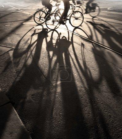 Photo pour Silhouette de cyclistes au lever du soleil, projetant de longues ombres - image libre de droit