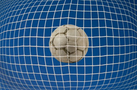 Photo for Closeup of football in a soccer goal net - Royalty Free Image