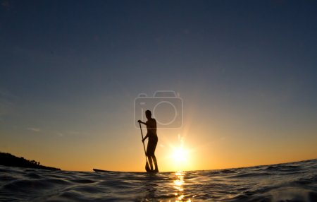 Silhouette of a man paddling his surf board at sunset