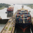 Several freighters, assisted by tugboats, are ente...
