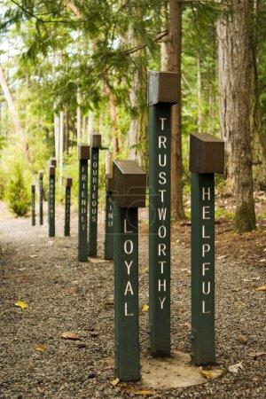 Photo pour Loyaux, dignes de confiance et serviables sont trois adjectifs qui décrivent les scouts. Ces panneaux bordent un chemin de terre menant à un terrain de feu de camp dans un camp de boy scout . - image libre de droit
