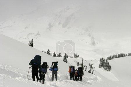 Photo pour Un groupe d'alpinistes ascendant Mt. rainier au milieu d'une tempête. le sommet sommet dead ahead est couvert de nuages. - image libre de droit
