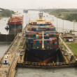 Two freighters, assisted by tugboats, are preparin...