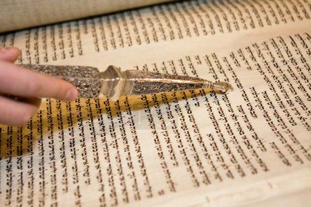 Photo pour Un vieux rouleau de la Torah en cours de lecture à une bar mitsva avec un yad traditionnel qui est nécessaire. Ce pointeur orné a un doigt à la fin qui pointe vers le mot . - image libre de droit