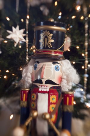 A traditional wooden nutcracker toy soldier with a...