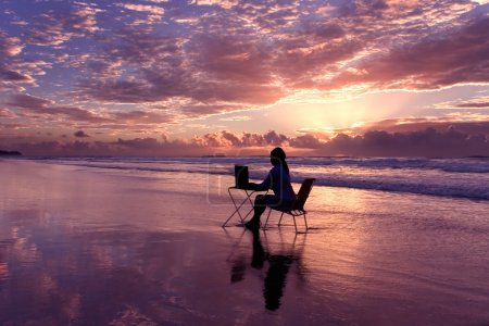 Photo pour Femme avec ordinateur portable travaillant au lever du soleil - image libre de droit