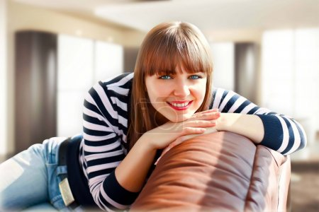 Photo for Young girl smile seats on the sofa - Royalty Free Image