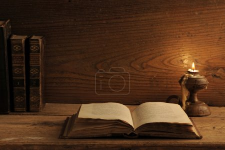 Photo for Old book on a wooden table by candlelight - Royalty Free Image