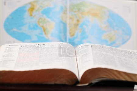 Bible open to the Book of Acts and a world map in ...