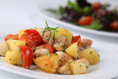 Fried potatoes with mushrooms and cherry tomatoes