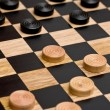 Checkers being played on wooden board...