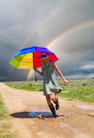Photo pour Fille de projections d'eau dans une flaque d'eau après la pluie - image libre de droit
