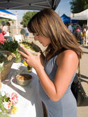 Pregnant Hispanic woman sniffing chamomile at the market