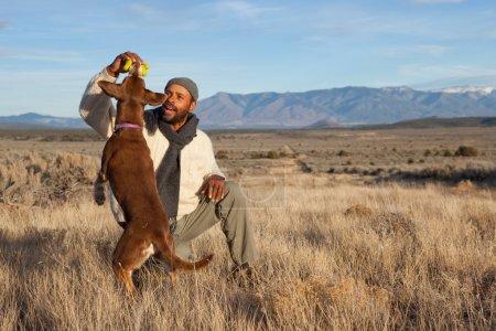 Photo pour Casual homme afro-américain, jouer avec son chien à l'extérieur - image libre de droit