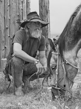 Photo for Authentic old school cowboy with his horse - Royalty Free Image