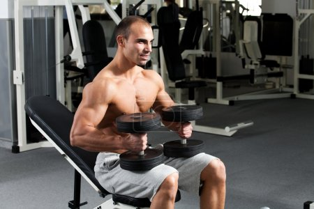 Photo for Young bodybuilder posing in the gym, with dumbbells in hands - Royalty Free Image