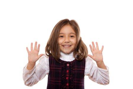Photo pour Portrait d'une jolie petite fille, souriante, montrant dix objets, habillée en uniforme scolaire, isolée sur fond blanc - image libre de droit