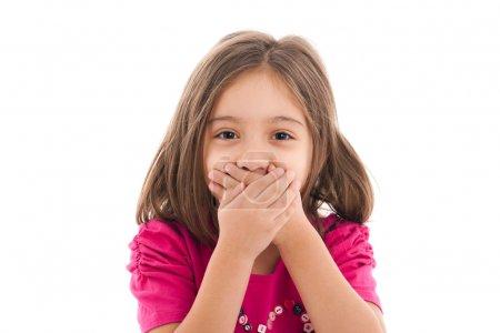 Foto de Retrato de una niña encantadora, cubriendo la boca con ambas manos, aislado sobre fondo blanco - Imagen libre de derechos
