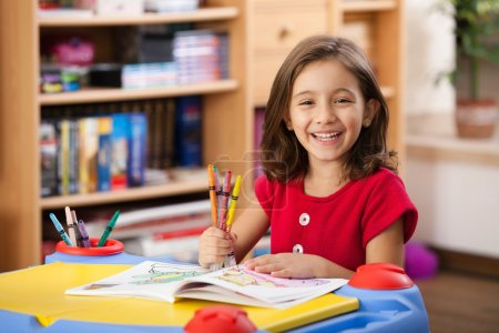 Photo for Little girl laughing, showing her colorful pencils at her playtable - Royalty Free Image