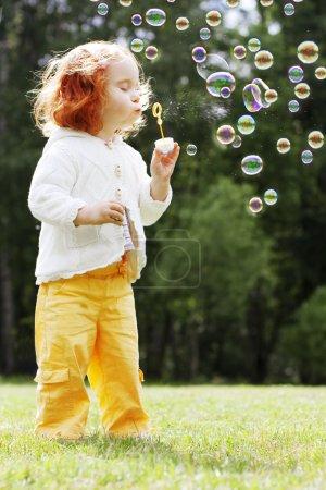 Photo pour L'image de la fille met les bulles dans le parc - image libre de droit