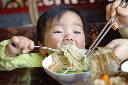 Photo pour Un bébé mignon mange - image libre de droit
