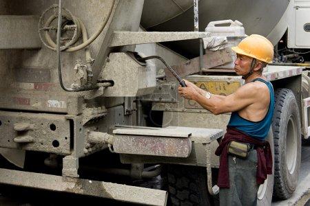 Photo pour Travailleur acharné et bétonnière sur chantier - image libre de droit