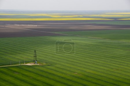 Foto de Vista aérea del único pozo de petróleo en campo verde cultivos - Imagen libre de derechos