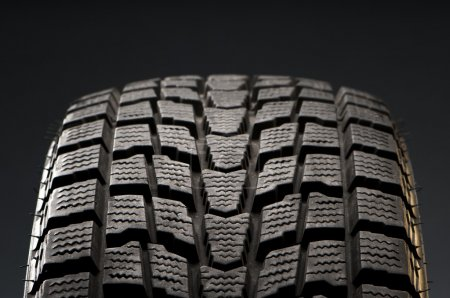 Photo for Closeup detail of black winter tire tread in studio shot - Royalty Free Image