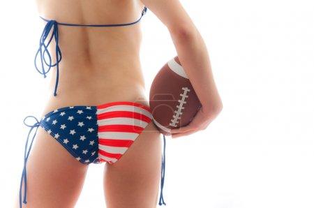 Photo pour Belle femme portant le drapeau des États-Unis bikini tenant un football isolé sur fond blanc - image libre de droit